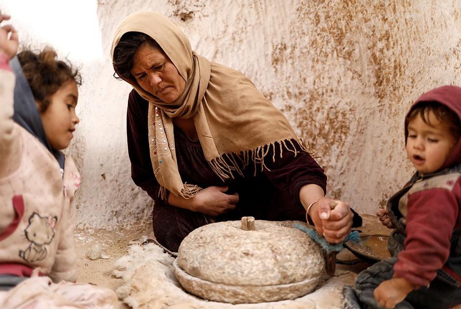 Салиха Мохамеди мелет пшеницу в своем подземном жилище в Матмате