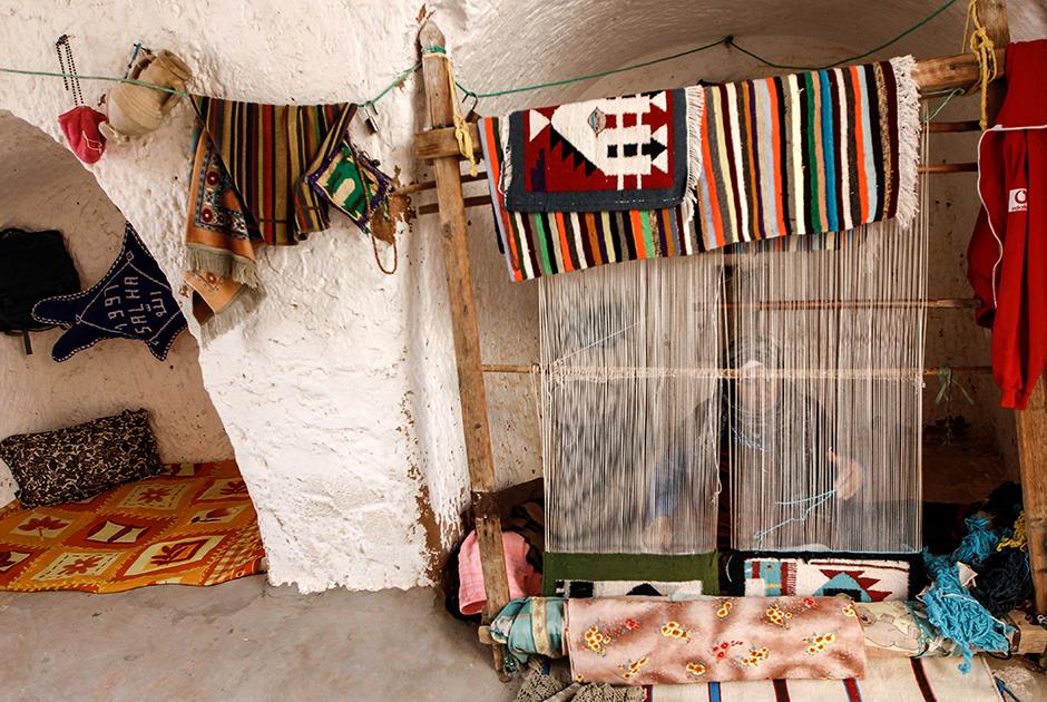 69-летняя Мунджия ткет ковер в своем подземном жилище в Матмате