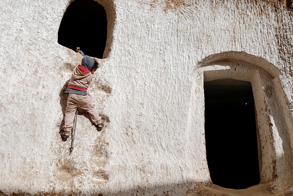 Четырехлетняя Ахлем карабкается по стене за кроликом