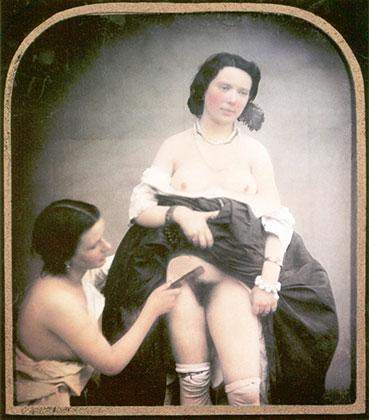 Полуобнаженная женщина расчесывает лобковые волосы другой женщины, стоящей рядом с ней с поднятой юбкой. 1850 год