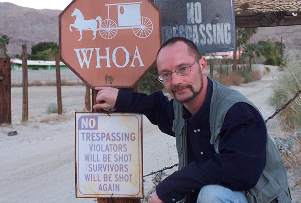 Автор на въезде в индейскую резервацию. Надпись на плакате: «Не вторгаться! Нарушители будут застрелены. Выжившие будут застрелены снова».