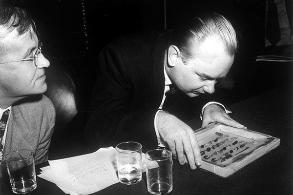 Former KGB officer Nikolai Khokhlov appears as a witness before the Senate Internal Security Subcommittee. Image shows Khokhlov examining a collection of bullets which contain poison. May. 21, 1954. (AP Photo)