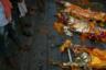Тела, ожидающие кремации, на ступенях гхата около воды Ганги.