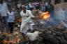 Родственник готовится поджечь тело усопшего, которое будет гореть около двух часов. Тела сжигают не до конца — мужчину до ребра, женщину — до бедра. Эти останки родственники должны торжественно предать Ганге в конце церемонии.