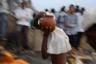 Родственник усопшего несет воду из священной Ганги к костру.