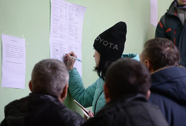 Женщина записывает номера мобильных телефонов родных и близких в списке пропавших без вести при пожаре в торговом центре «Зимняя вишня» в Кемерово.