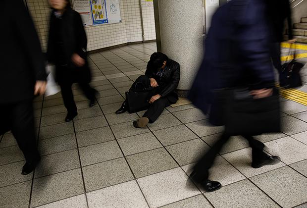 Спящий человек на станции метро в Токио