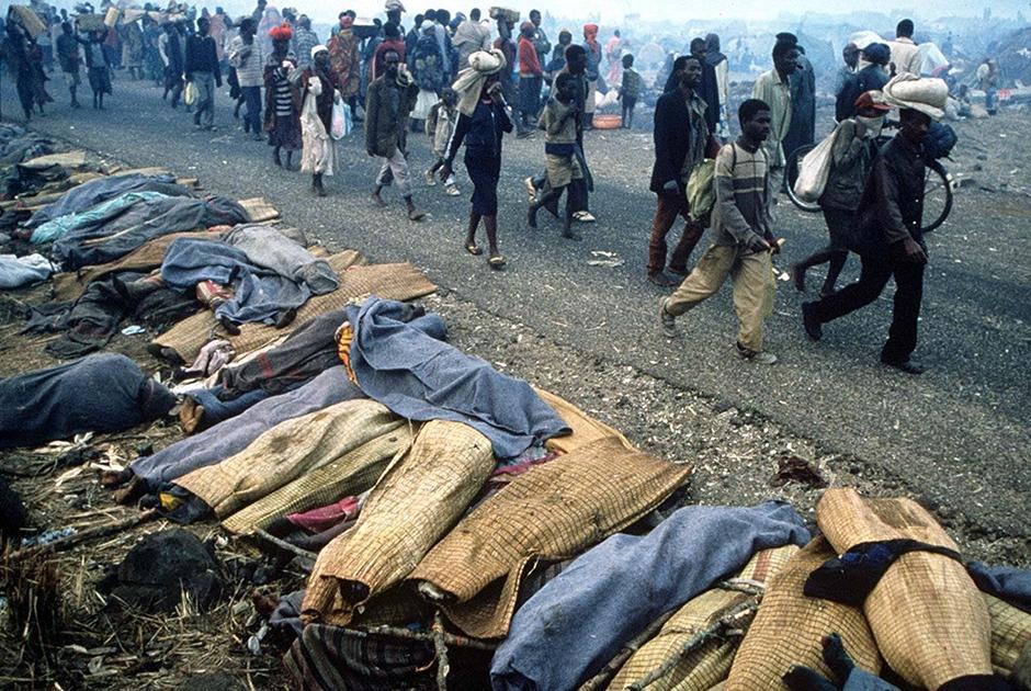 Беженцы проходят мимо тел десятков убитых в Руанде в 1994 году