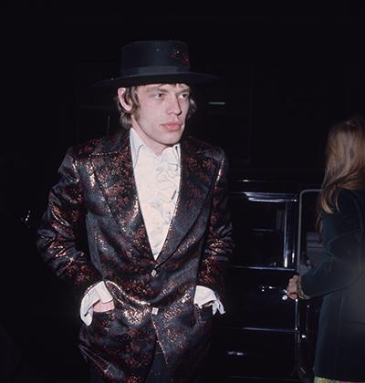 В 1967-м Мик Джаггер мог позволить себе куда более смелые эксперименты. Кожаное пальто, рубашка с жабо, шляпа, длинные волосы и бакенбарды — в таком виде музыкант явился на балет.