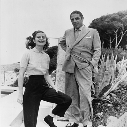Главная пара Греции —Аристотель Онассис и его жена Афина Ливанос в 1955 году. На бизнесмене типичный для 50-х годов двубортный пиджак, а вот краги на ботинках характерны скорее для 30-х.