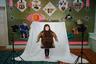 Девочка в традиционном костюме в игровой комнате.