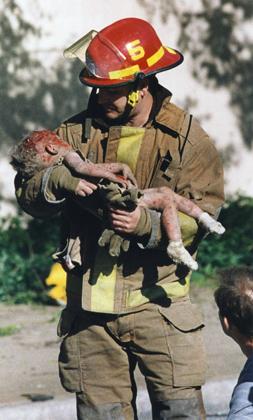 Пожарный Крис Филдс с пострадавшей при взрыве девочкой, которая позднее скончалась. Фотография стала символом теракта. За нее была присуждена Пулитцеровская премия.
