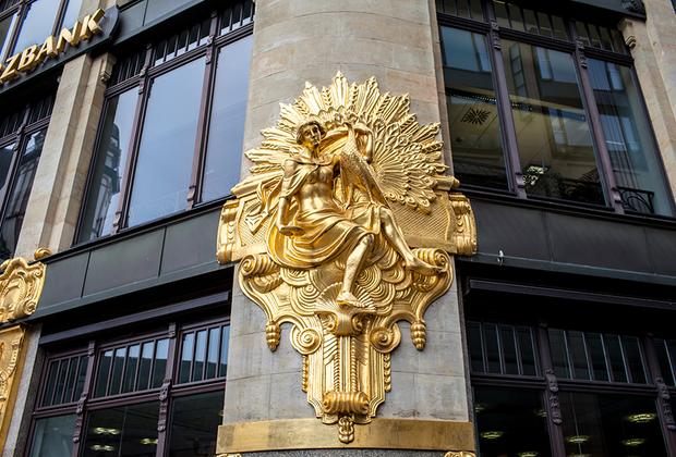 Здание банка с «золотыми» фигурами, которое было изначально построено как универмаг. На фасад несколько раз покушались желающие поживиться золотом, попытки прекратились лишь после того, как через газеты было официально объявлено, что в составе скульптур золота нет.