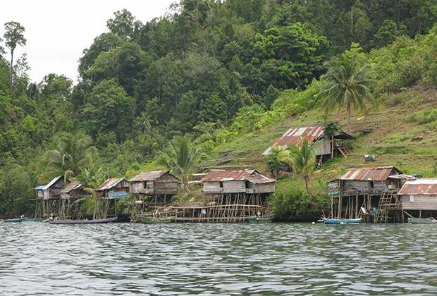 Домики на сваях на склоне горы. Жилая деревня на одном из мелких островов