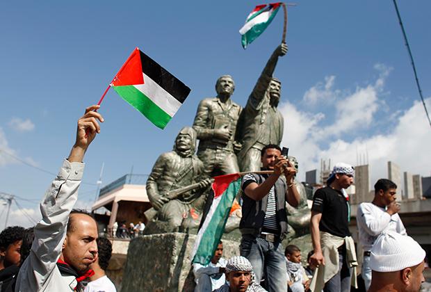 Сирийцы с палестинскими флагами около Голанских высот, завоеванных Израилем у Сирии