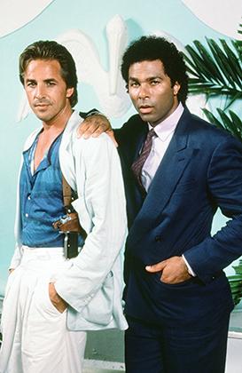 Дон Джонсон и Филипп Майкл Томас — главные звезды сериала Miami Vice в типичных образах: дорогой деловой костюм на герое Томаса и куда более демократичный «лук» Джонсона.