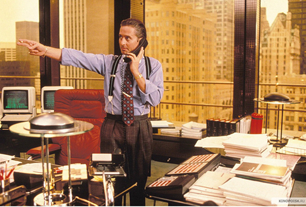 Один из культовых «луков» эпохи — главный герой фильма «Уолл-Стрит» Гордон Гекко в исполнении Майкла Дугласа. Фиолетовая рубашка с закатанными рукавами, яркий галстук, брюки на подтяжках, зализанные волосы, золотые часы и зажим для галстука — ни у кого не должно возникнуть сомнения, что у этого человека много денег.