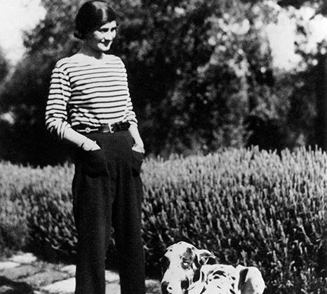 Дизайнер Шанель стала одной из первых, кто позволил женщинам превратить мужской стиль одежды из сугубо спортивного в круизный и коктейльный. Она шила брюки из саржи не только клиенткам, но и себе, и носила их на отдыхе, комбинируя с бретонской тельняшкой и эспадрильями. Например, прогуливалась в таком неформальном виде с псом Гиго на своей вилле La Pausa в Рокбрюне.
