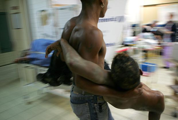 Венесуэлец несет раненого друга в отделение скорой помощи