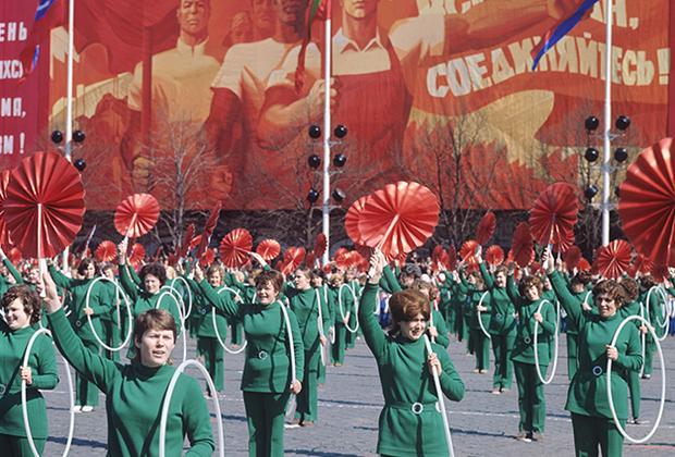 Первомайские демонстрации на заре СССР были показом завоеваний коммунизма, а на его излете — добровольно-принудительным народным гуляньем с признаками официального оптимизма. Для главной демонстрации страны на Красной площади унифицированные костюмы шили ведущие советские дома моды. Брюки в 1970-е были синонимом стиля и прогрессивности не только на Западе, но и в СССР.