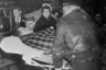 Сенатор Джон Ф. Кеннеди после операции на позвоночнике. В больнице сказали, что состояние сенатора остается «хорошим» и он проведет несколько месяцев после выздоровления в доме отца, бывшего посла в Великобритании Джозефа П. Кеннеди. Миссис Кеннеди и брат сенатора, Эдвард, наблюдают за транспортировкой.