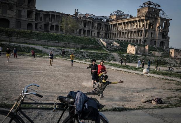 Молодежь играет в футбол возле разрушенного дворца Амина. На площадке рядом — игроки в крикет, не попавшие в кадр. Пономарев отмечает, что именно крикет — любимый уличный спорт в этом регионе.   <br> <br>  Дворец разбомбили еще в 1979 году во время штурма советскими военными. Восстанавливать его не стали.