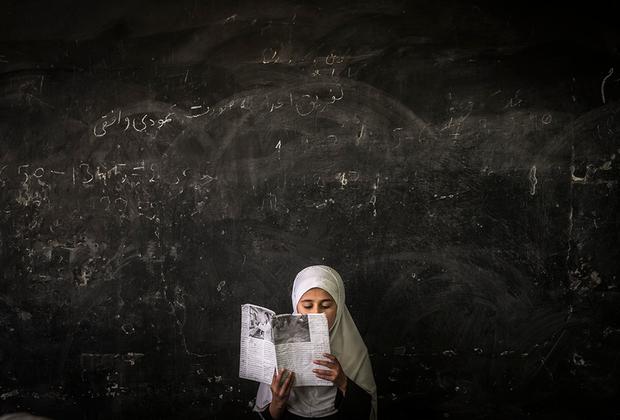Афганская девушка читает книгу перед классом в школе в центральной провинции Парван.