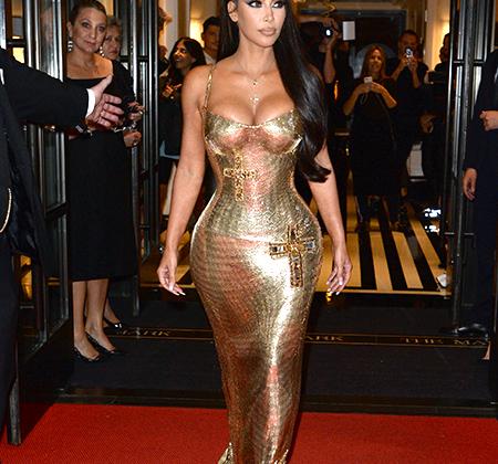 В отличие от своей сестры Кендалл Дженнер, надевшей брюки, Ким Кардашьян предпочла платье. Много золота, глубокое декольте, огромный крест на бедре, все от Versace — армянский шик калифорнийского разлива.