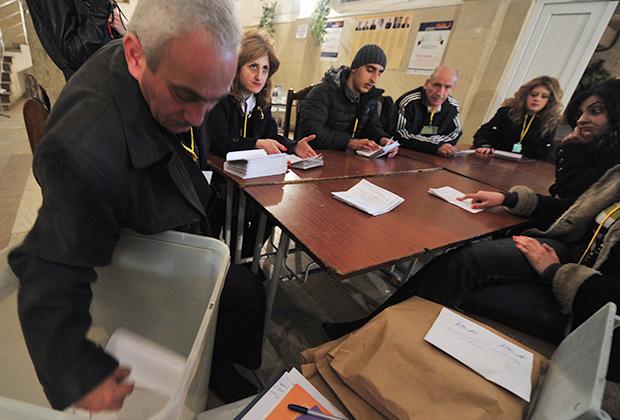 Сотрудники участковой избирательной комиссии в Ереване подсчитывают бюллетени после окончания выборов президента Армении