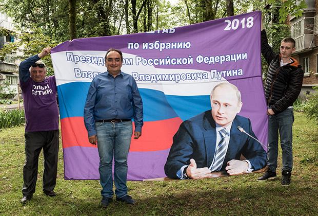 Марат Динаев (в центре) на фоне флага «Отрядов Путина»