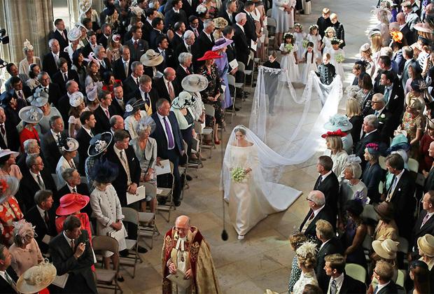 """Большую часть пути к алтарю Меган Маркл прошла одна, лишь в конце ее взял под руку принц Чарльз. Ее отец Томас Маркл не смог приехать из-за сердечного приступа, последовавшего за <a href=""""https://lenta.ru/news/2018/05/14/batya/"""" target=""""_blank"""">скандалом</a> с подсадными фотографиями."""