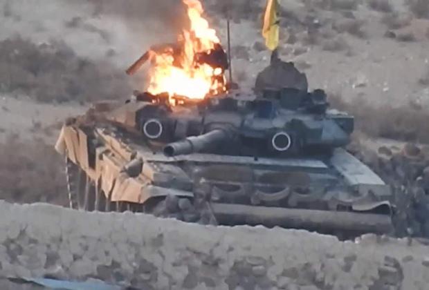 Горящий танк Т-90А со знаменем «Харакат Хезболла ан-Нуджаба» во время боев с «Исламским государством» в районе Ханассера