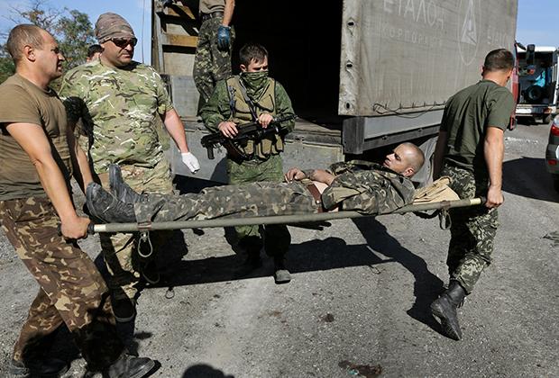 Украинские военные несут своего раненого товарища. Он умрет через полчаса после того, как сделано фото