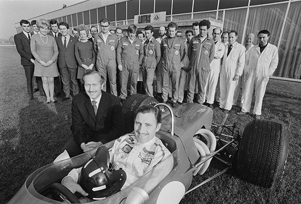 В 1968 году Грэм Хилл в составе команды Lotus стал чемпионом второй раз в карьере. Грэм был уже немолод, но его опыта и скорости машины хватило для титула. В конце 60-х Хилл еще игнорировал всеобщую моду на длинные волосы и выглядел едва ли не консервативнее, чем его босс Колин Чэмпен (сидит рядом с машиной).
