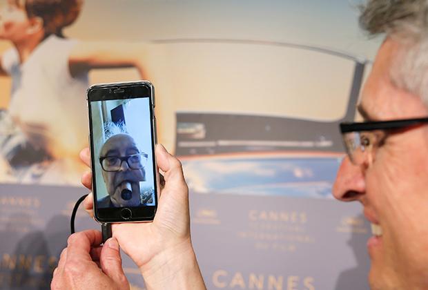 Продюсер Фабрис Араньо держит свой смартфон во время пресс-конференции с Жан-Люком Годаром 12 мая 2018 года на Каннском фестивале.
