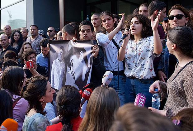 Собравшиеся у здания прокуратуры держат плакат с портретами убитых школьников