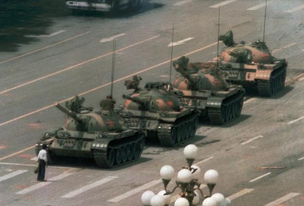 """Одна из самых знаменитых фотографий, изображающих события тех дней, — «Неизвестный бунтарь». По легенде, мужчина с авоськами полчаса сдерживал колонну танков, направлявшихся в центр столицы. Снимок сделал репортер агентства Associated Press с шестого этажа гостиницы «Пекин». Кадр облетел весь мир и был напечатан во множестве изданий, в том числе в журнале Time, который включил одинокого бунтаря в список 100 самых влиятельных людей XX века.  <br><br> Телеканал CNN публиковал <a href=""""https://www.youtube.com/watch?v=YeFzeNAHEhU"""" target=""""_blank"""">видео</a> с места событий, на котором видно, как мужчина не дает танку себя объехать, преграждая ему путь, и яростно машет руками, отгоняя бронетехнику. Затем он взбирается на танк и пытается достучаться до военного внутри. Вдалеке в это время уже слышны выстрелы.  <br><br> Большинство китайцев никогда не видели этого фото и не знают о существовании видеозаписи. Ролик показали по китайскому телевидению всего раз. Тогда диктор уверенным голосом убеждал телезрителей: «Если бы наши танки хотели проехать, этот нарушитель бы их точно не остановил. Это видео показывает истинное лицо западной пропаганды и подтверждает, что наши военные проявили невероятную сдержанность»."""
