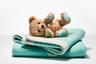 Милый символический подарок для новорожденного: мишка Тедди с пяточками фирменного бирюзового оттенка Tiffany и серебряным сердечком с узнаваемой гравировкой. Легкое одеяльце все того же бирюзового цвета — идеальное дополнение.