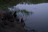 Отец с сыном ловят рыбу в озере. Рыбалка — одно из немногих семейных развлечений в поселке.