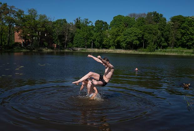 Мальчишки плавают в озере после школьных занятий.