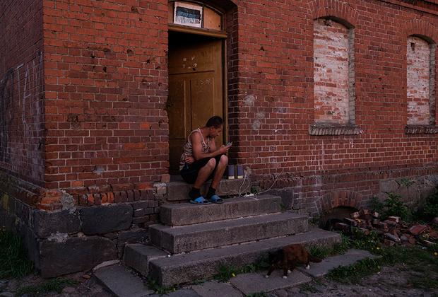 Местный житель слушает музыку на крыльце одного из четырех аварийных немецких домов.