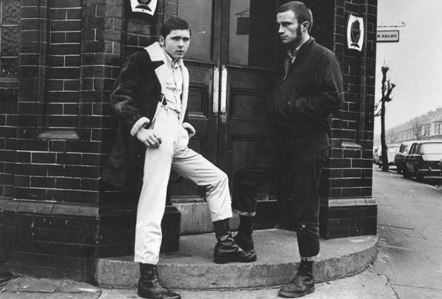 Первые скинхеды носили достаточно длинные волосы. Для стрижки использовались насадки №2 и реже №3. Некоторые даже носили бакенбарды. Опознать скинхедов в этой паре проще всего по ботинкам, подвернутым джинсам и брюкам, а также подтяжкам.