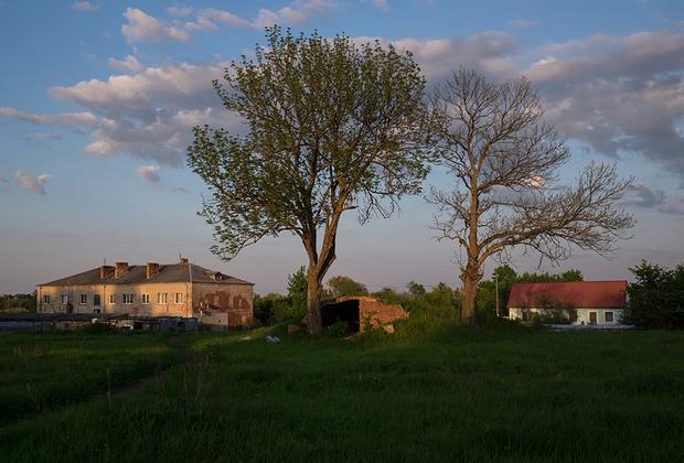 Жилые здания и заброшенный немецкий бункер около старой железной дороги.