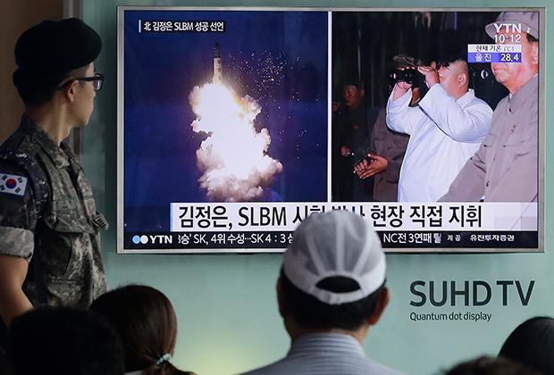 Солдат армии Южной Кореи смотрит выпуск новостей о запуске очередной северокорейской ракеты. 2016 год