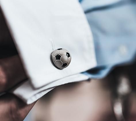 Новые запонки из серебра с черной эмалью российской марки Gourji выпущены к мундиалю и предлагаются в двух версиях — с матовым покрытием либо родированные. Крошечный мячик вращается на ножке, как в подкрученном ударе. Тираж — 1964 пар.