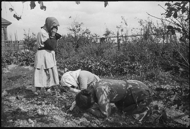 Вернувшиеся в освобожденную деревню жители плачут над могилами убитых немцами родственников. Район Ржева.