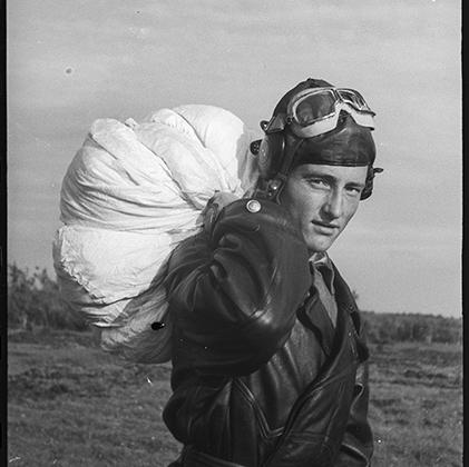 Гвардии сержант летчик-истребитель Лавренко, протаранив немецкий самолет, благополучно спустился и возвращается в свою часть, неся на плечах парашют. Калининский фронт.