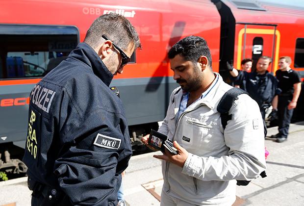 Полицейский проверяет документы у мигранта