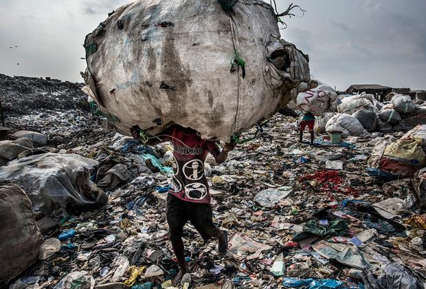 Мусорный кризис постепенно окутывает всю планету. Люди производят столько отходов, сколько никогда прежде не производили. Ежедневно в мире появляется 3,5 миллиона тонн твердых отходов, что в 10раз превышает уровень прошлого столетия. Только американцы ежемесячно отправляют на свалку мусор, равный весу своего тела. Такими темпами к концу XXI века ежедневный объем отходов на планете может достигнуть 11 миллионов тонн.   <br> <br>  Мусорный коллапс во всех красках оказался в объективе нидерландского фотографа Кадира ван Лохёйзена. Он изучил, как проблема с мусором решается в шести крупных мегаполисах мира — Джакарте, Токио, Лагосе, Нью-Йорке, Сан-Паулу и Амстердаме. Фотограф пришел к выводу, что до сих пор далеко не все осознают, что отбросы можно использовать вторично.  <br> <br>  Лидером по отходам среди всех городов мира является Нью-Йорк: 33 миллиона тонн в год, что в 15 раз превышает показатель Лагоса, в котором, однако же, проживает гораздо больше людей. На снимке — один из пяти тысяч работников лагосской свалки Олусосан, занимающей 45 гектаров. Среди гор мусора они ищут пластик и другие материалы, которые можно отправить на переработку.  <br> <br>  Ежедневно на Олусосан свозят от трех до пяти тысяч тонн мусора. Полигон переполнен, и городские власти планируют его закрывать. Однако другой свалки нет, а инфраструктуры для переработки отходов недостаточно. Лохёйзен подмечает, что нигерийские свалки пахнут значительно меньше, чем другие подобные по всему миру, поскольку жители страны выбрасывают меньше продуктов. Они либо все доедают, либо отдают оставшееся животным.