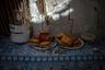 Алтарь с подношениями— калмыцкие борцоки (пончики из сдобного теста), сладости, фрукты, калмыцкий чай джомба, монеты, свечи.